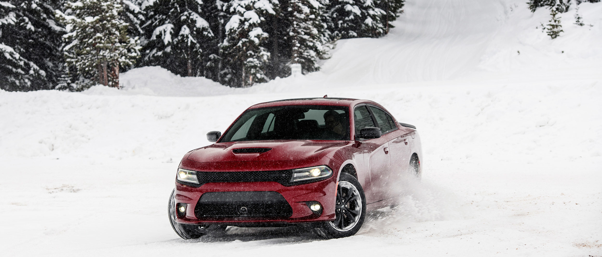 Burgundy Dodge Charger at the bottom of a snowy hill with snow-covered trees in the background.