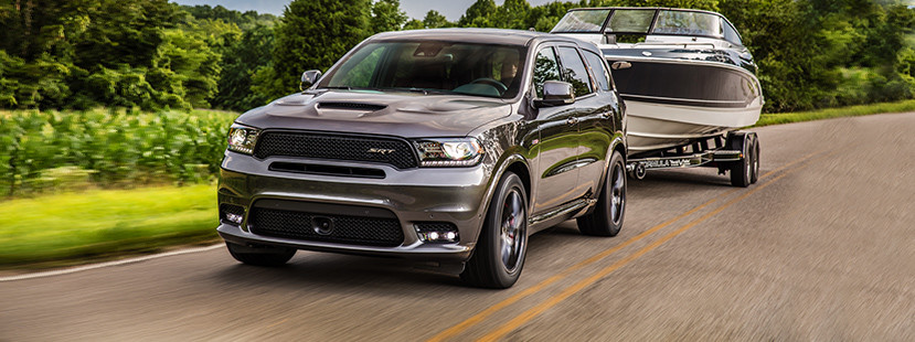 Grey 2019 Dodge Durango towing a black-and-white boat through a countryside.