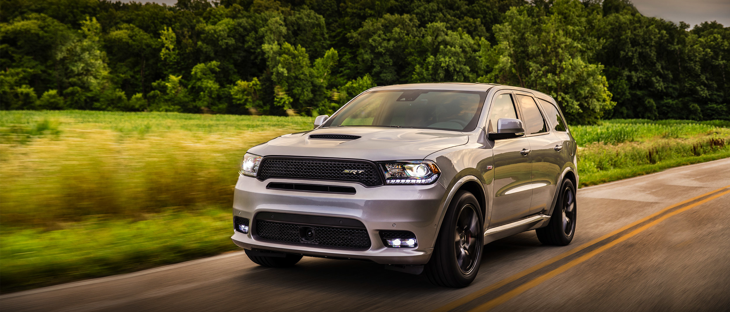 Grey 2020 Dodge Durango being driven on a country road next to a field and trees