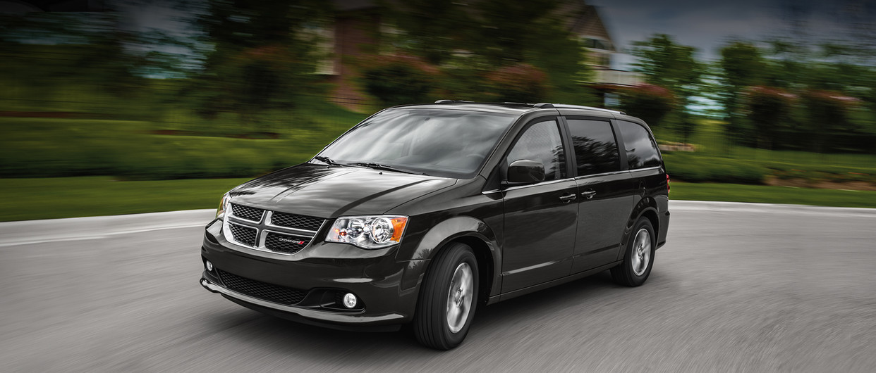 Front view of a grey 2020 Dodge Grand Caravan driving down a residential street