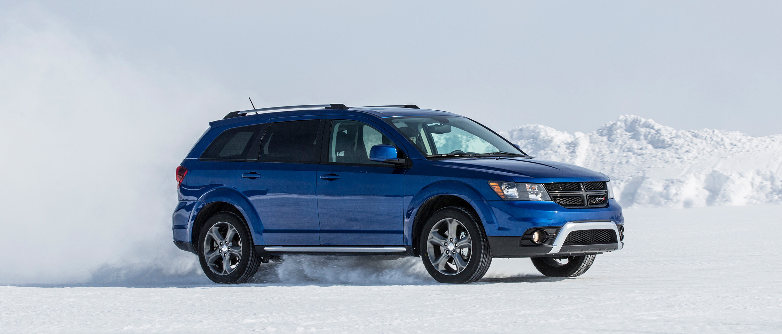 Side view of the blue 2019 Dodge Journey driving through a snowy field in the mountains