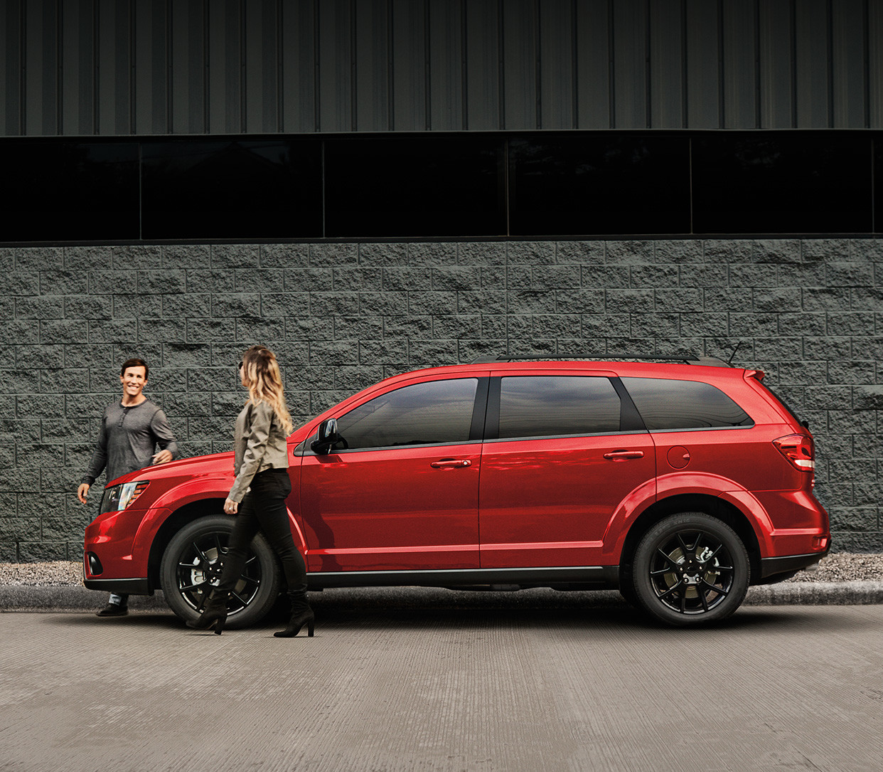 Red 2019 Dodge Journey, parked beside a grey building with two people walking away from the vehicle.