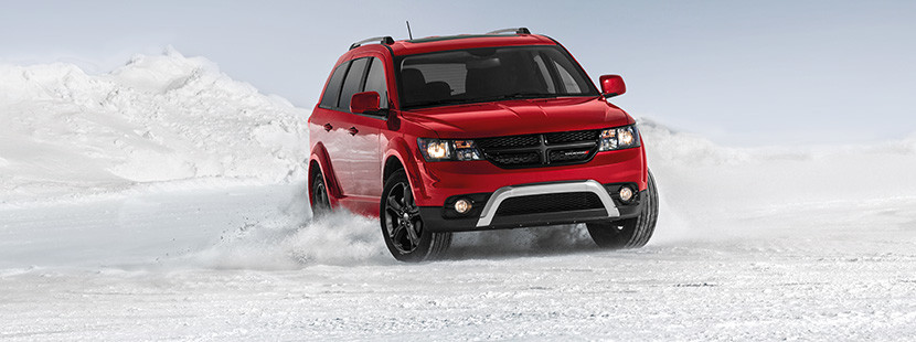 Front view of the red 2019 Dodge Journey driving through a snowy field