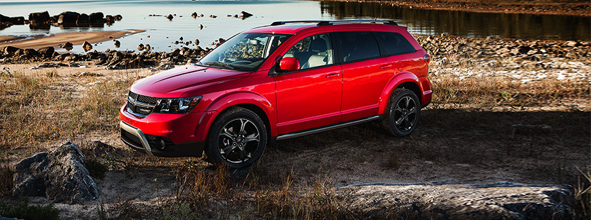 Red 2019 Dodge Journey, parked on a rocky lake shore.