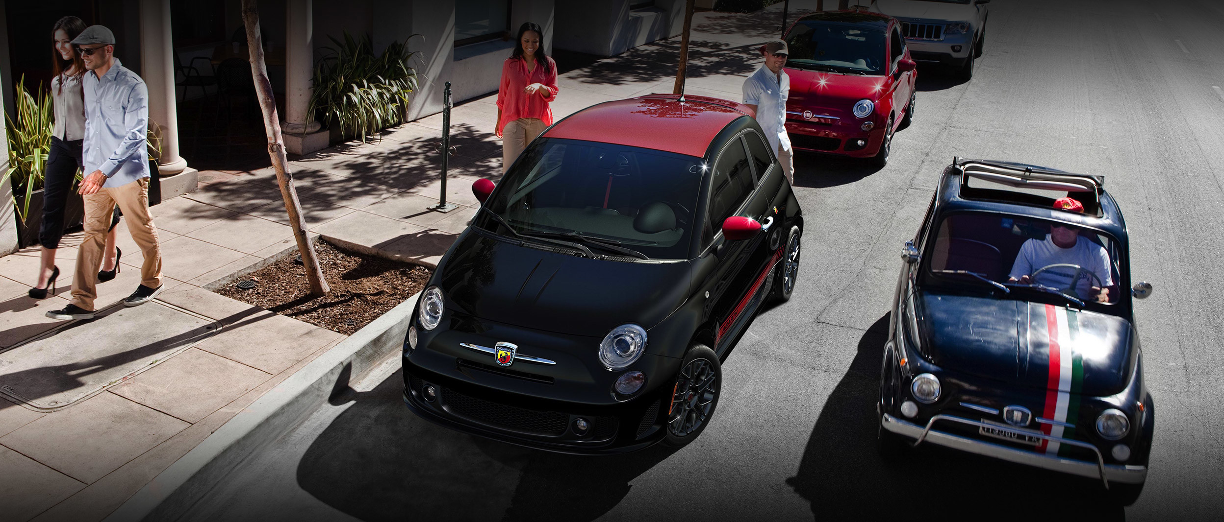 Black and red 2019 FIAT® 500 parked on the side of a street with a woman getting ready to enter the car.