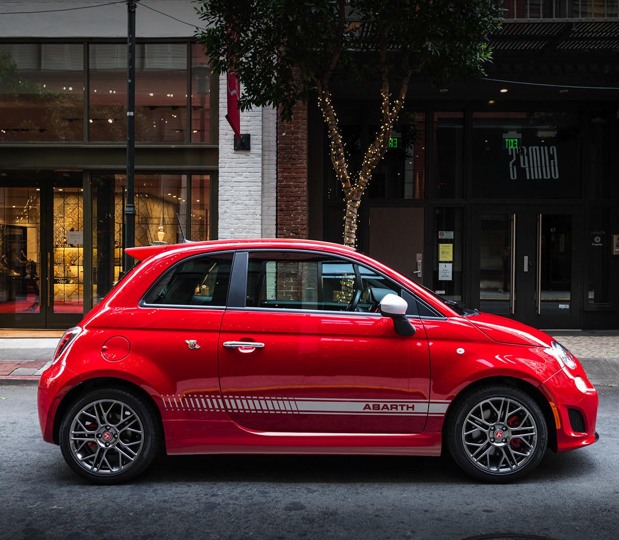 Red 2019 FIAT® 500 parked on the street in a city.