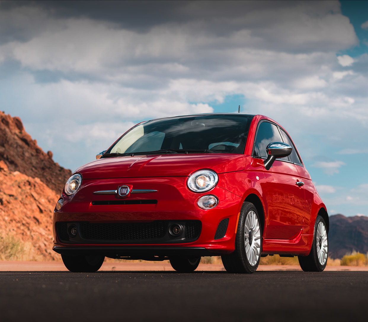 Red 2019 FIAT® 500 parked on a road outdoors by mountains.