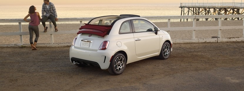Rear view of the white 2019 FIAT 500 parked by the beach with the sunroof down, as a couple sits on a fence nearby