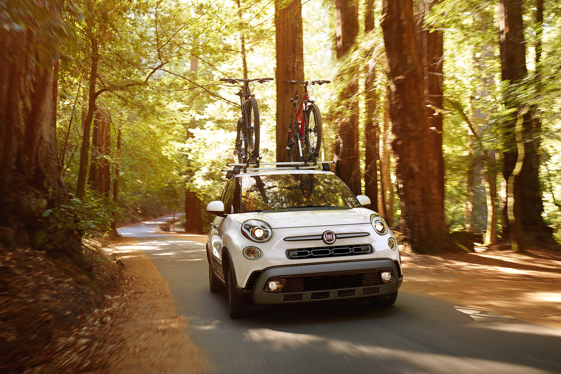 2019 Fiat 500L front view driving down country road, shown in white