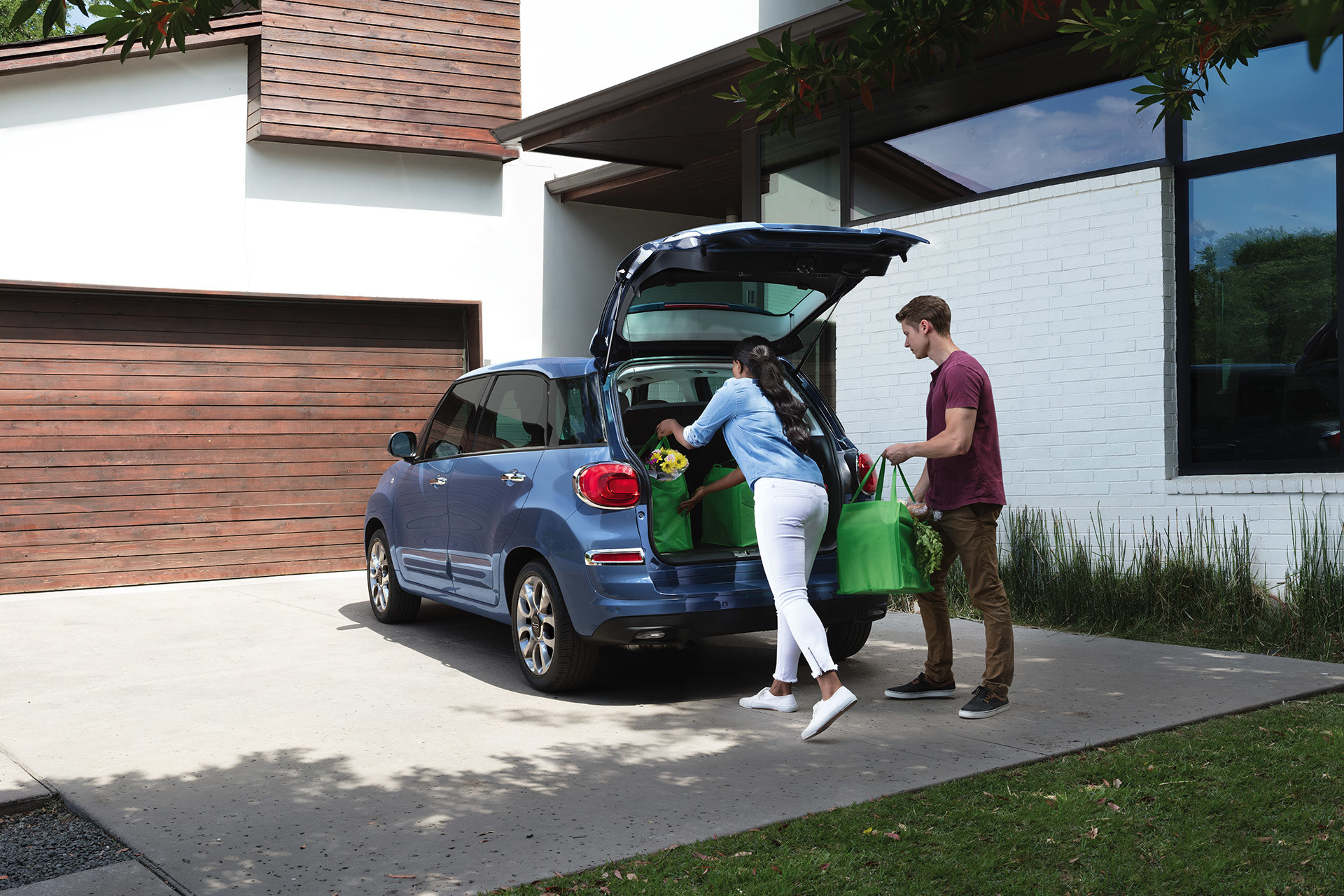 2019 Fiat 500L exterior shot of two people unloading the trunk, shown in blue