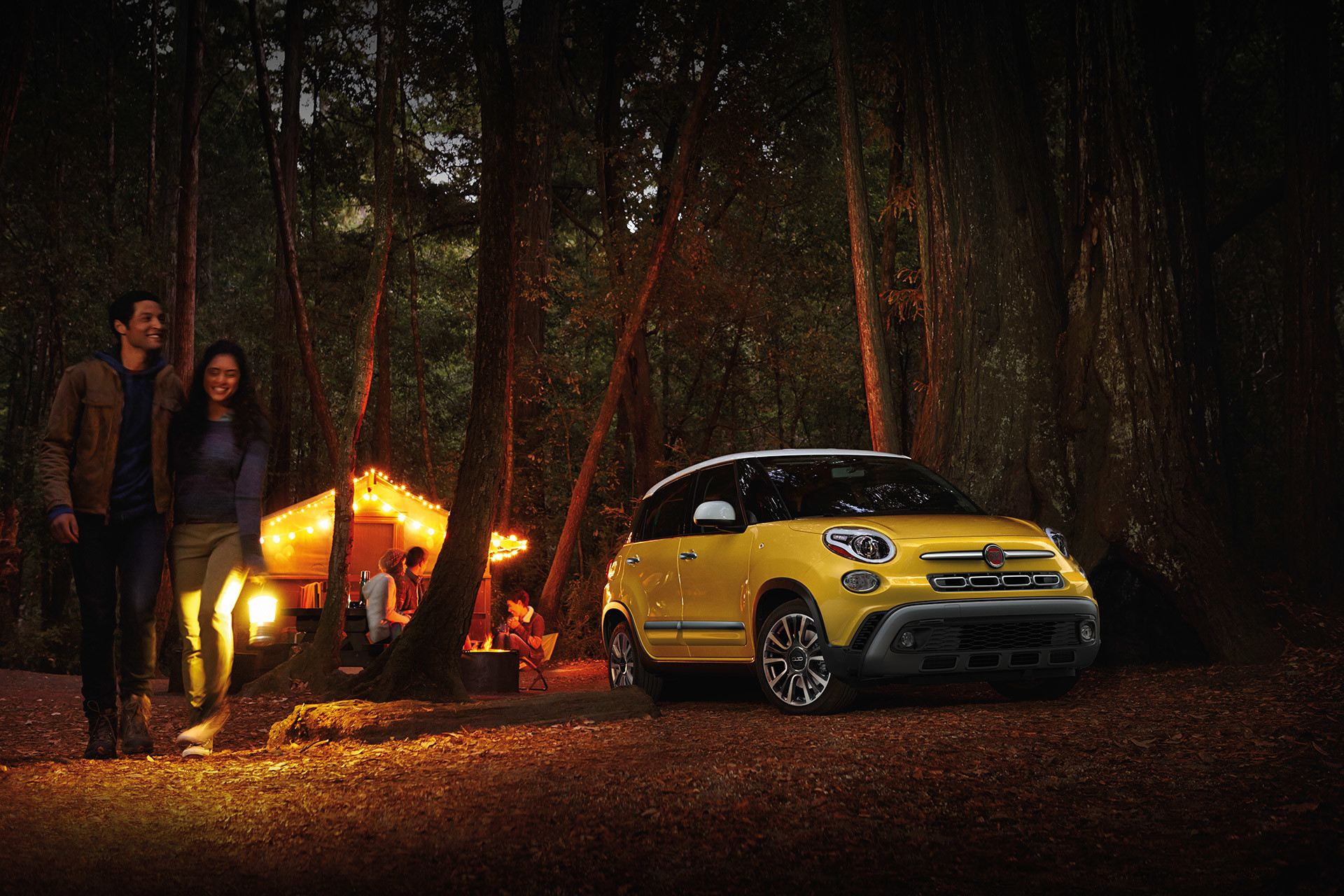 2019 Fiat 500L parked in forested area at night, shown in yellow