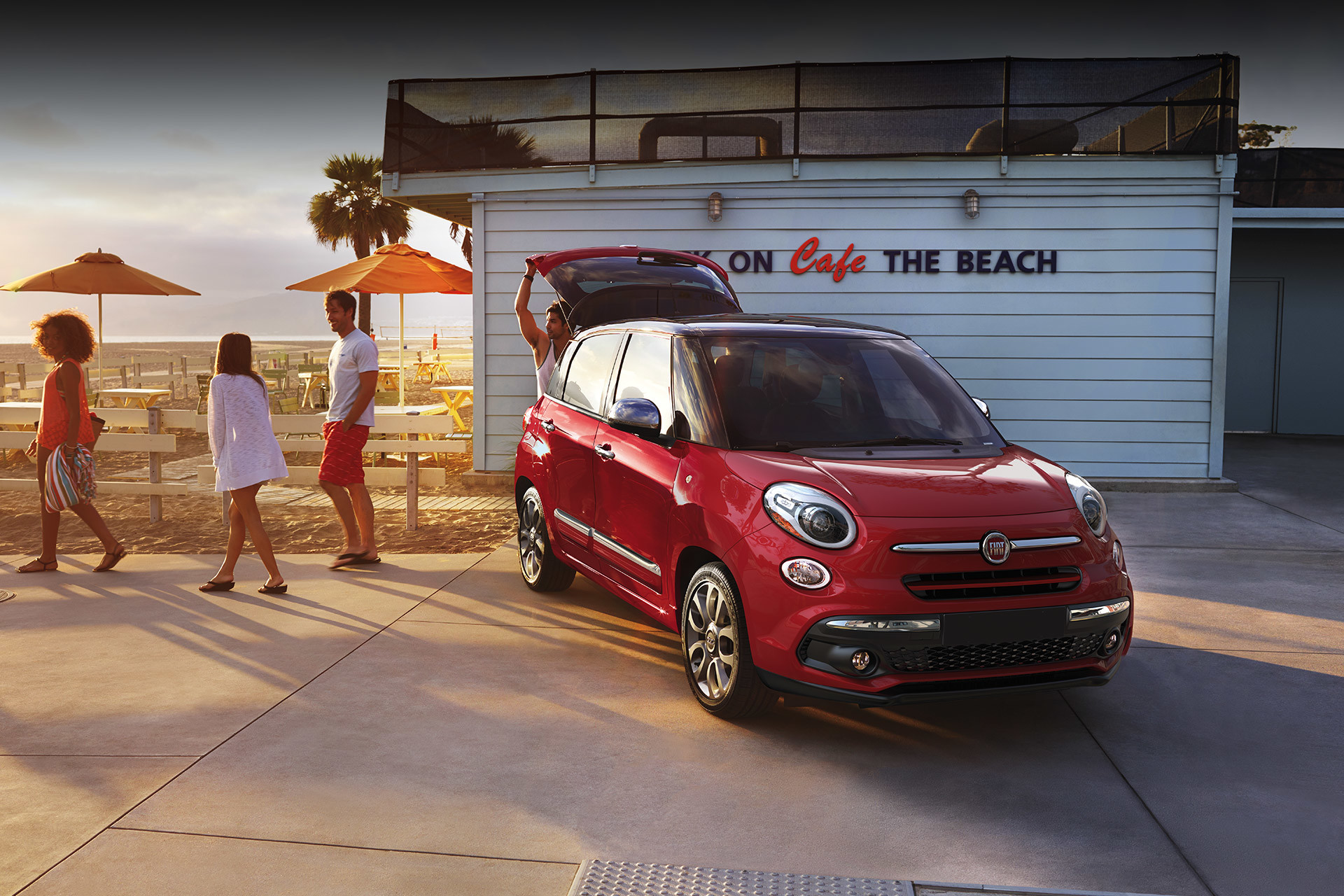 2019 Fiat 500L parked on beach boardwalk with trunk open, shown in red