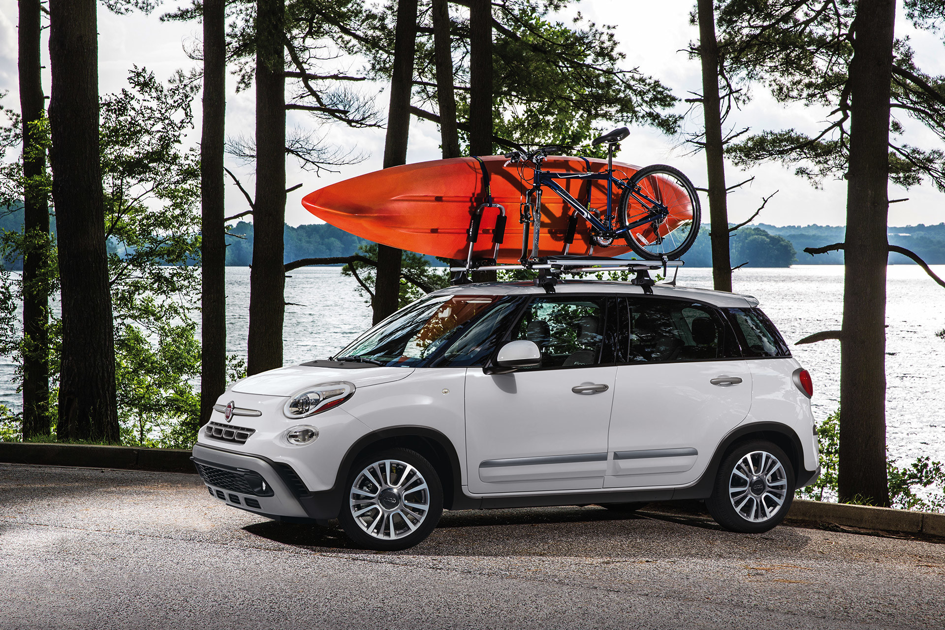 2019 Fiat 500L parked by a lake with a bicycle and kayak on the roof, shown in white