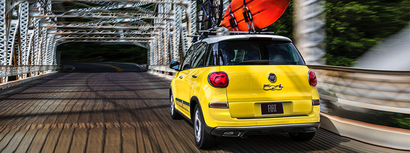 2019 Fiat 500L crossing a bridge, kayak and bicycle on the roof, shown in yellow