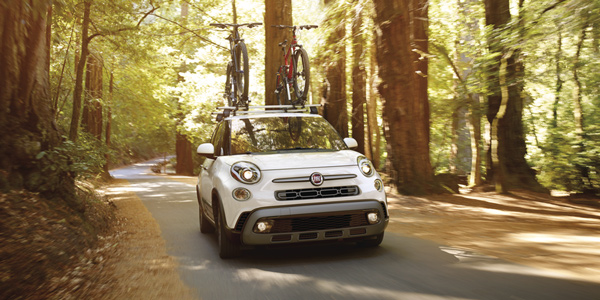 White 2020 Fiat 500L with mountain bikes on the roof rack driving through the forest