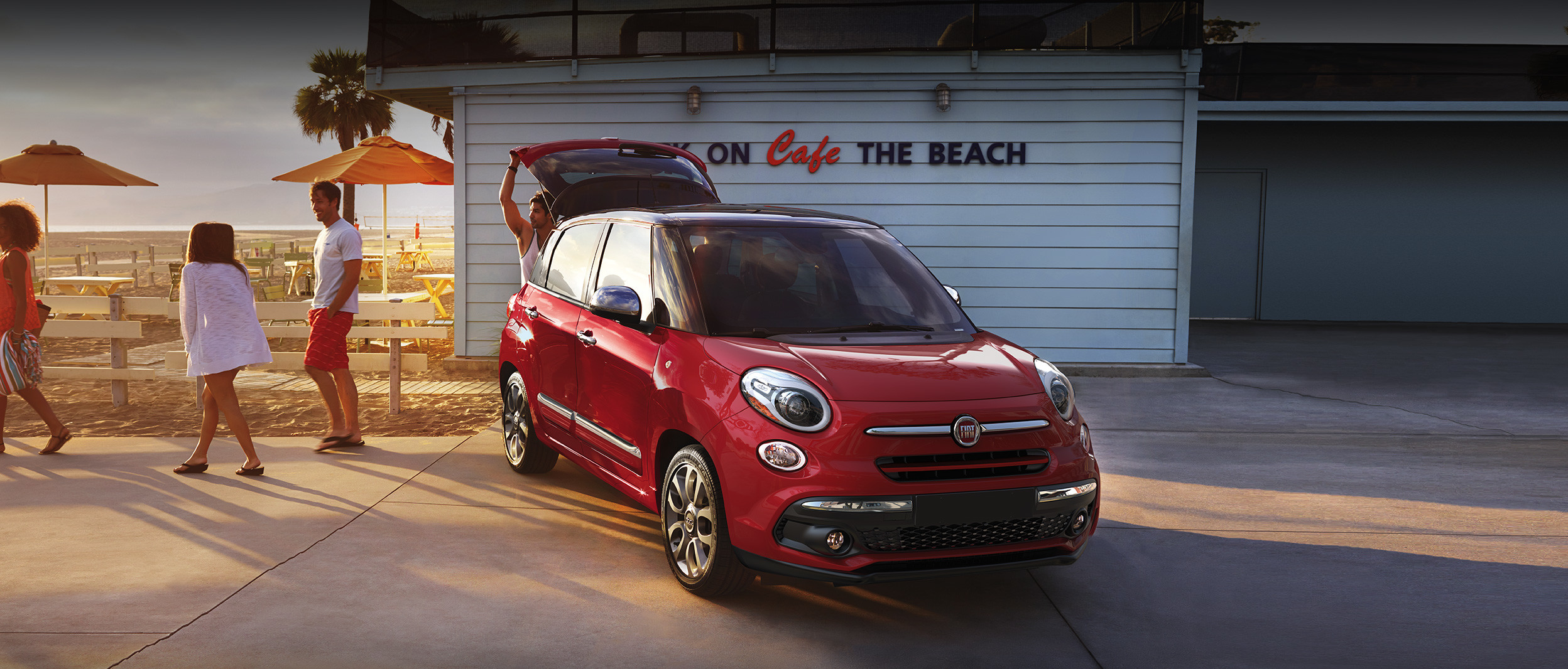 The 2020 Fiat 500L parked on a driveway beside two people during the sunset