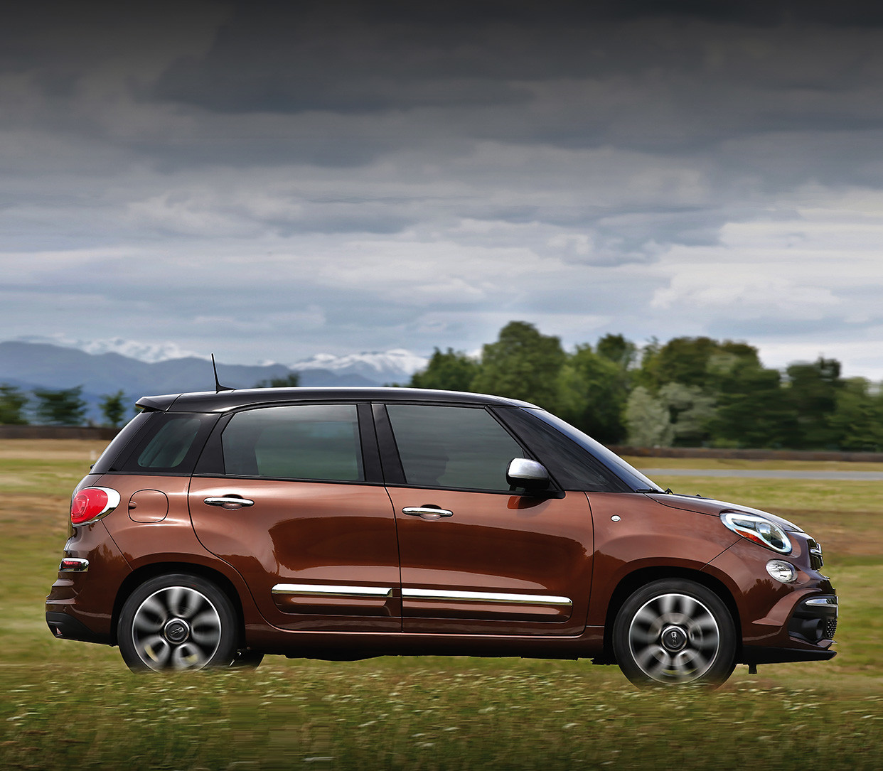 Side view of the 2020 Fiat 500L being driven on a country road through plains