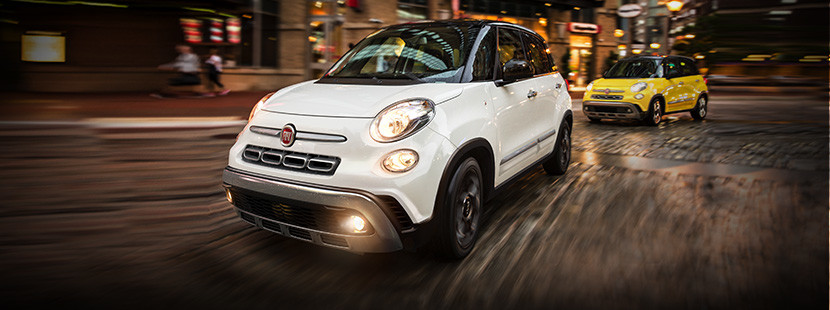 Front view of the white 2020 FIAT 500L driving on a city street