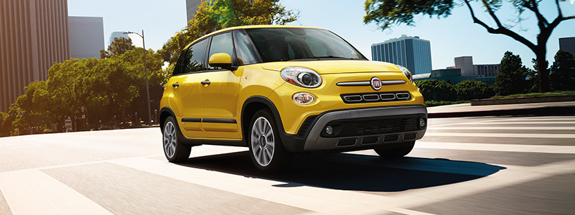 Front view of the yellow 2020 FIAT 500L driving down a road in a city