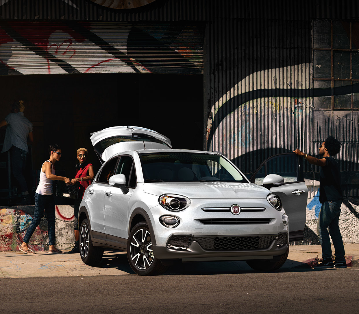 The white 2020 Fiat 500X parked at the loading bay while people loading cargo