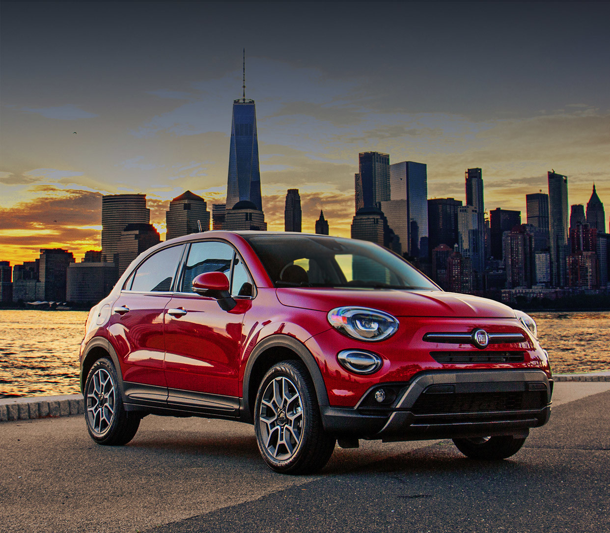 The red 2020 Fiat 500X parked outdoors near lake in front of urban scenery