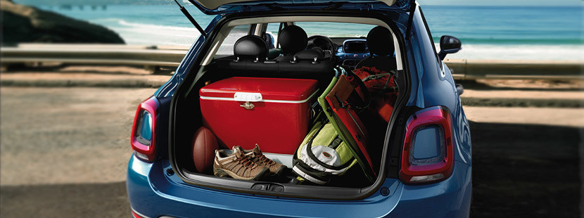 The trunk cargo space of the blue 2020 FIAT 500X loaded with camping gear parked by the beach with the tailgate open