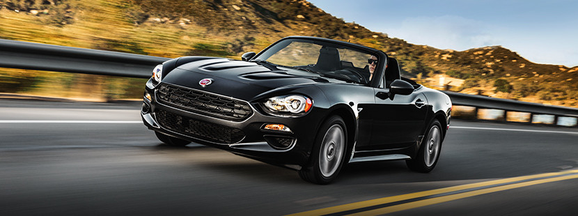 2019 Fiat 124 Spider driving down highway, shown in black