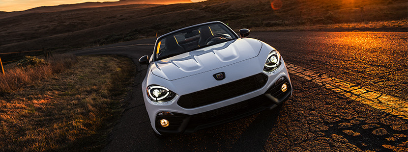 2019 Fiat 124 Spider front view driving down highway, shown in white