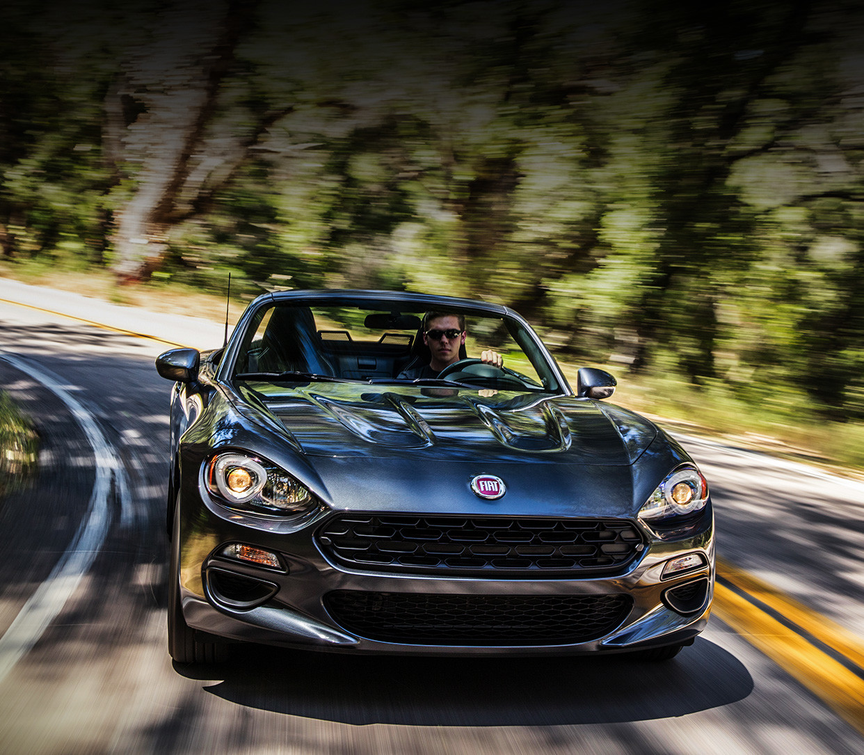 White 2020 FIAT 124 Spider being driven on a country road in a sunset