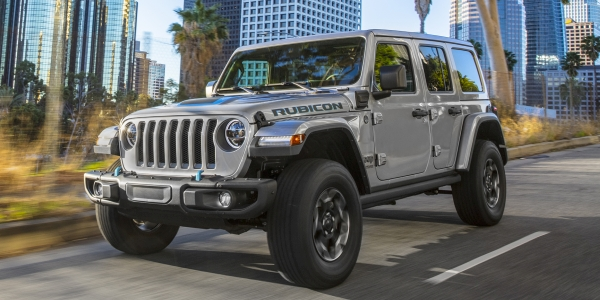 The New 2021 Jeep Wrangler 4xe being driven on the highway with the city behind.