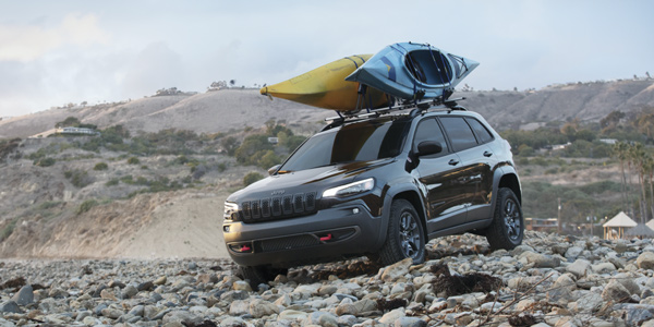 Black 2020 Jeep Cherokee with kayaks on the roof rack driving through a rocky area