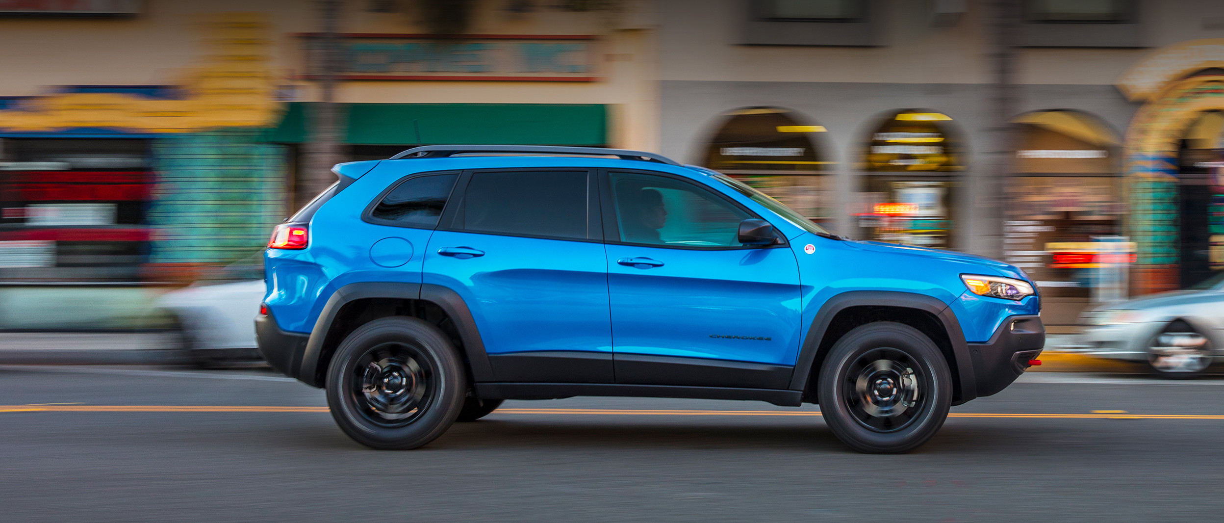 2020 Hydro Blue Pearl Jeep Cherokee driving on a country road through plains in the sunset