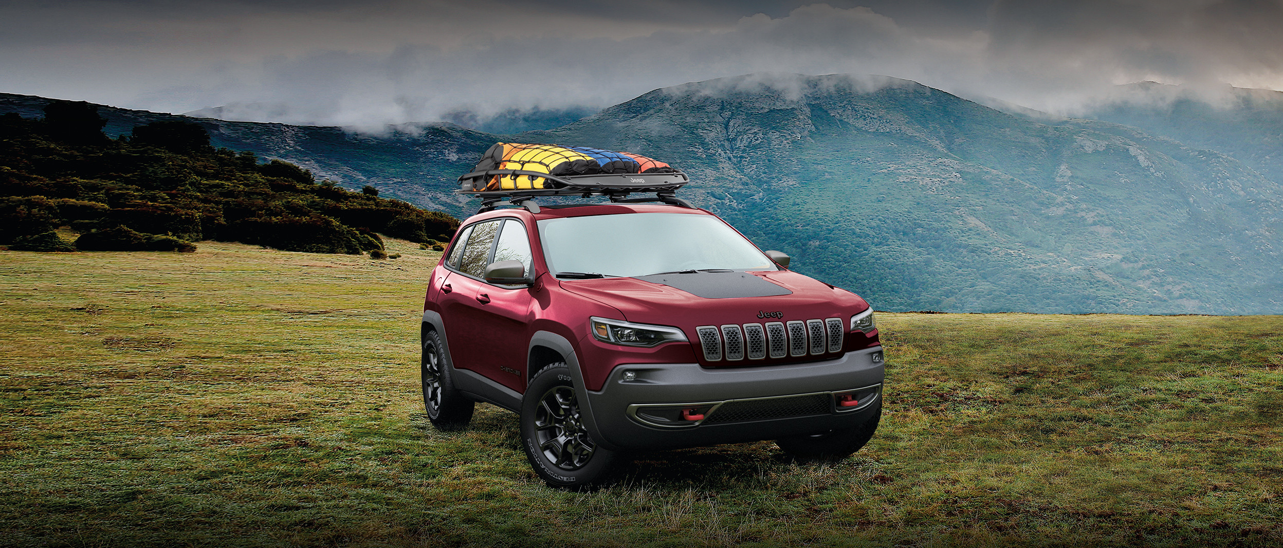 2020 Jeep Cherokee trailhawk parked on a grass field surrounded by mountains