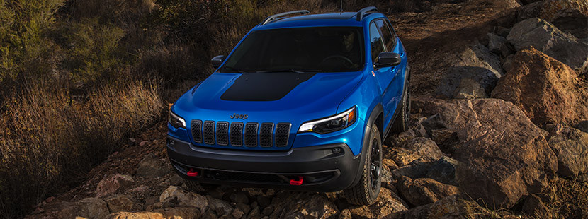 2020 Jeep Cherokee being driven on off road surrounded by mountains during daytime