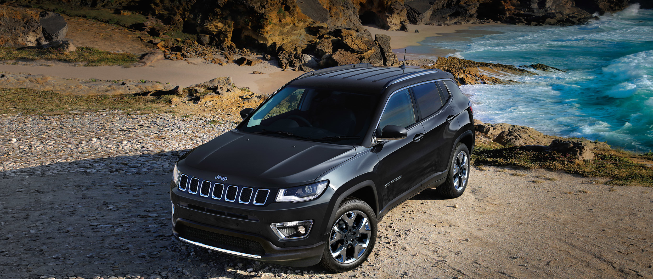 Black 2019 Jeep Compass, parked on a rocky beach.