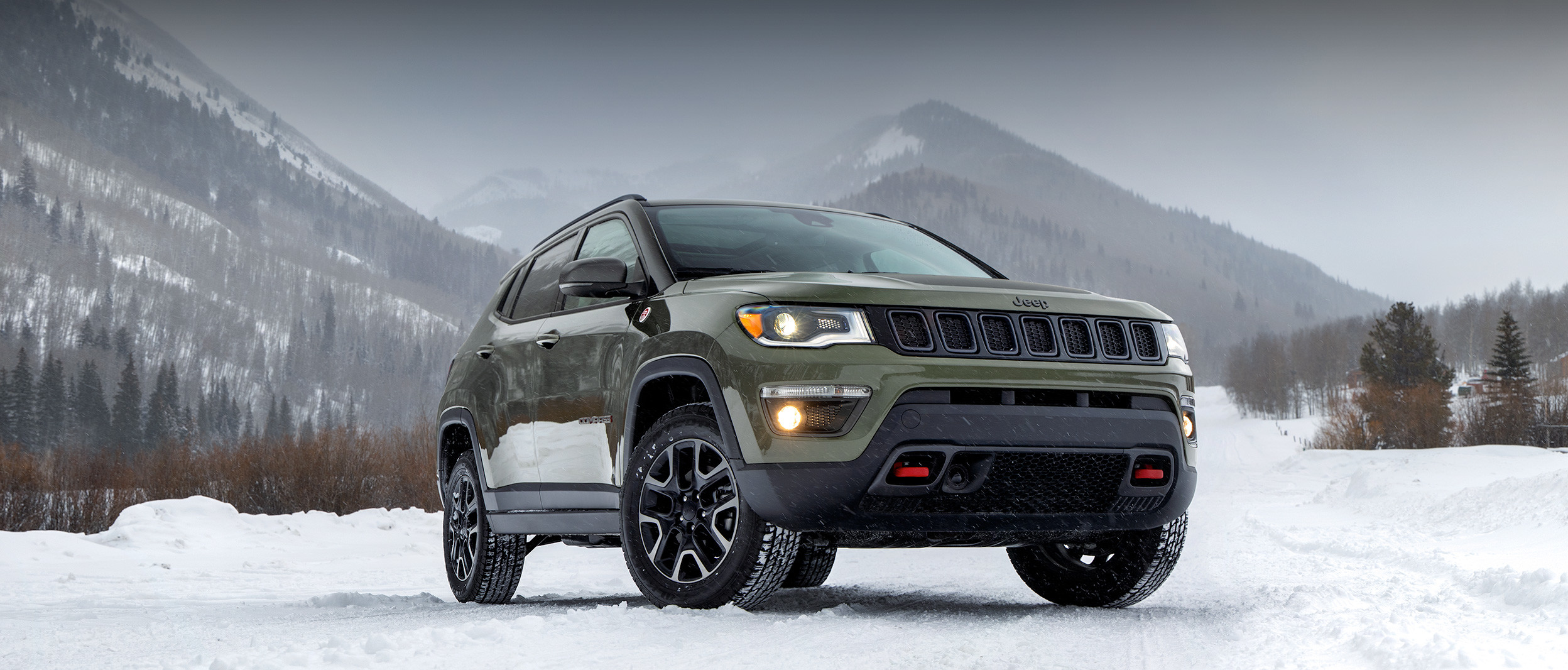 Front view of the 2020 Jeep Compass Trailhawk in green parked on a snow-covered road in front of mountains