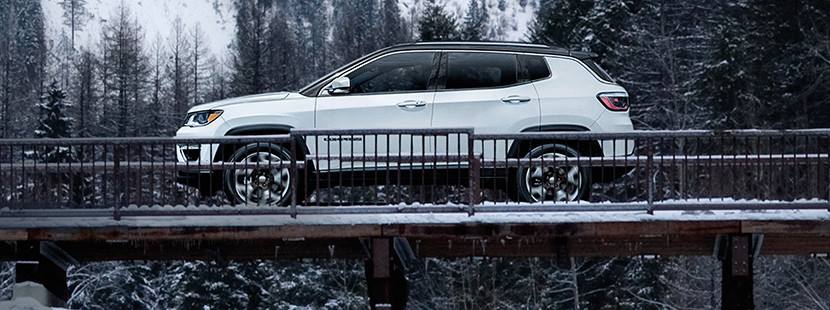 Side view of the white 2020 Jeep Compass passing through a snow covered bridge in the mountains