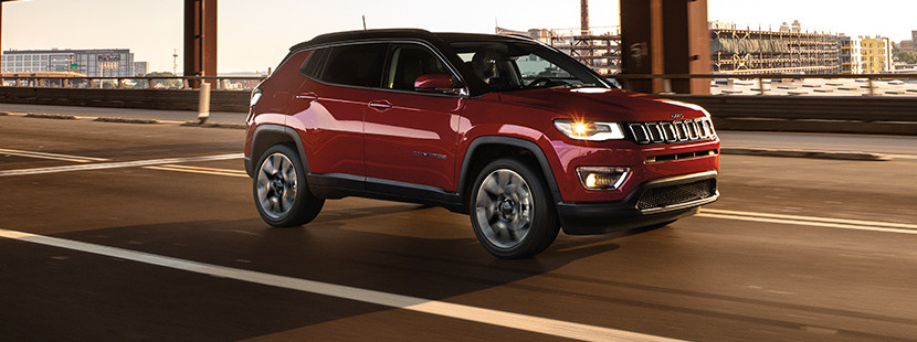 Red 2019 Jeep Compass being driven on a city road.