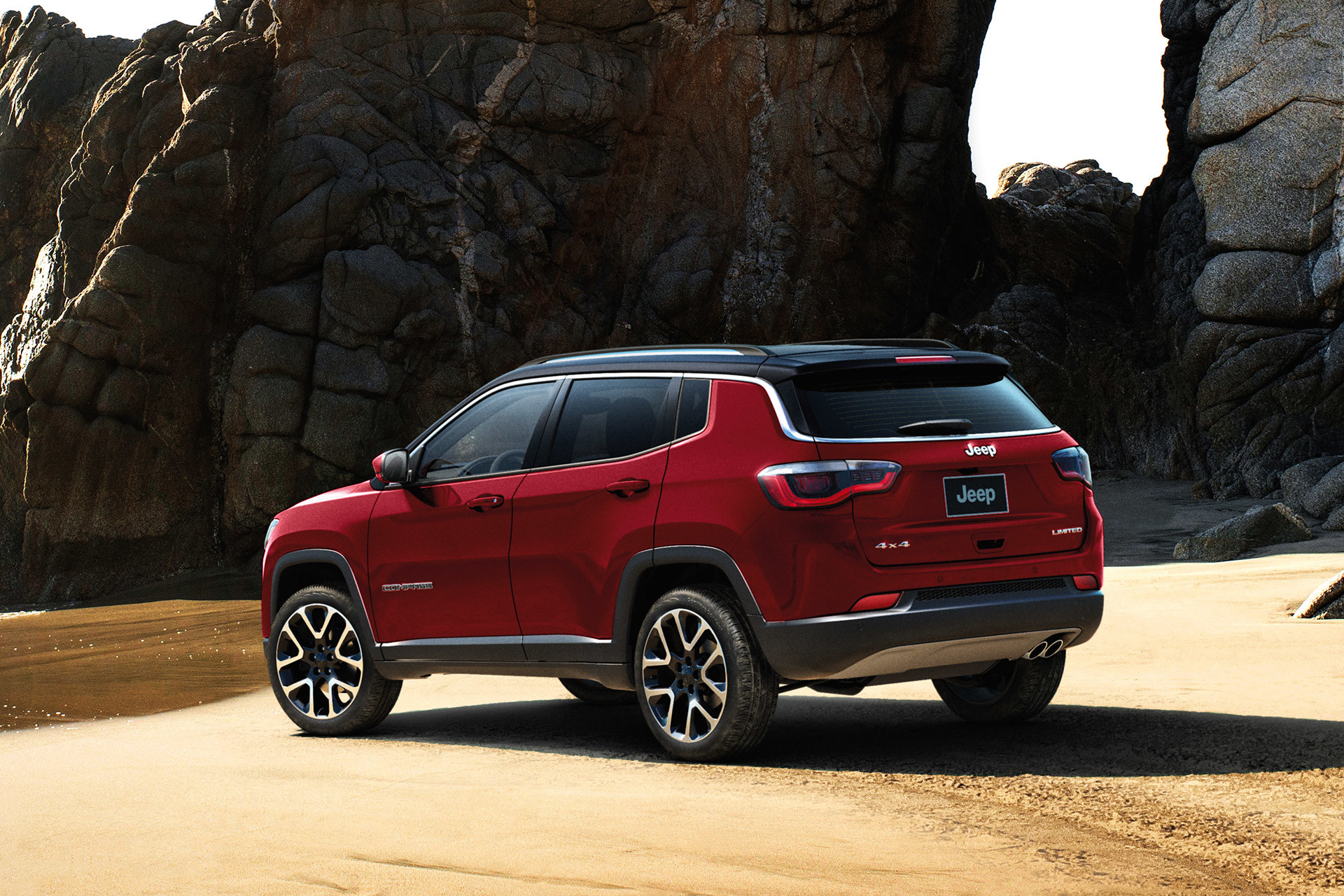 Red 2020 Jeep Compass parked on a beach with large boulders in the background.