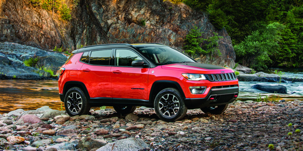 Red 2020 Jeep Compass driving through a rocky area using 4x4 capabilities