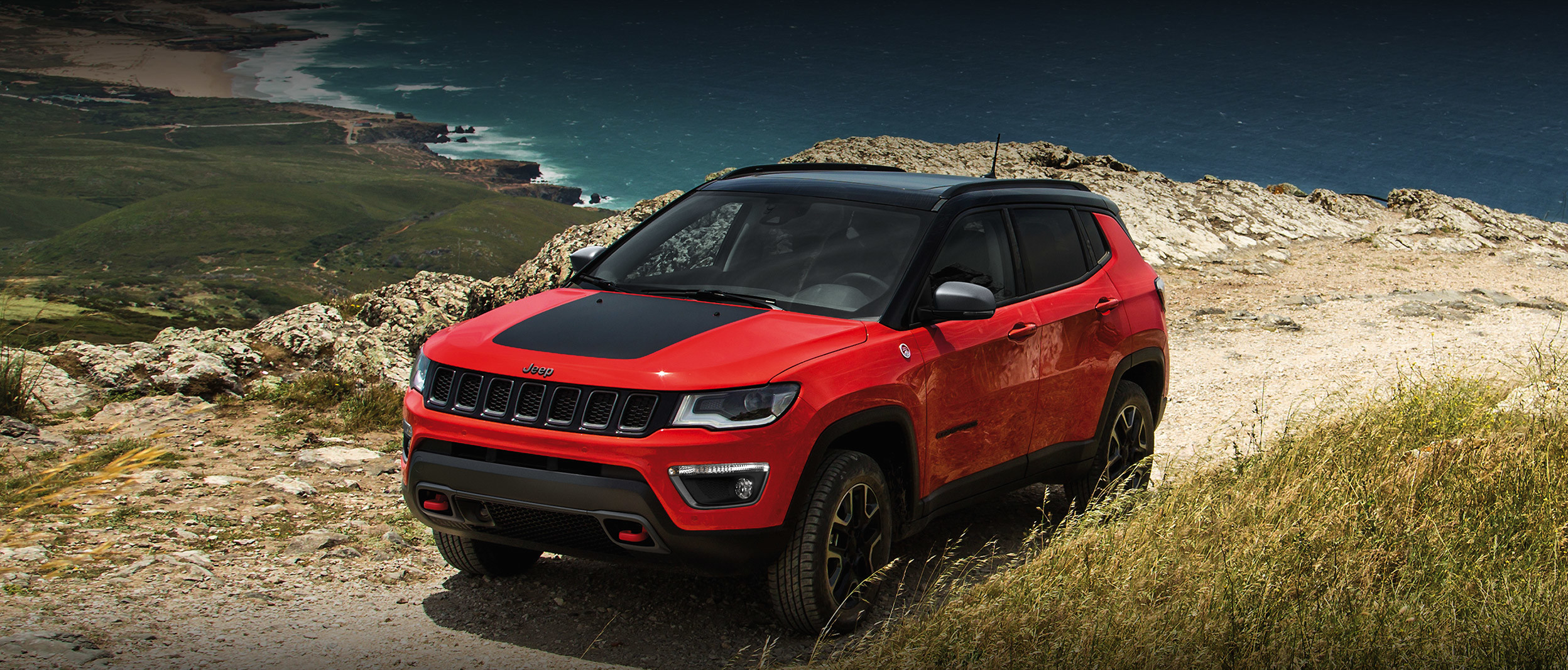 Red 2020 Jeep Compass parked on a sandy road by the beach.