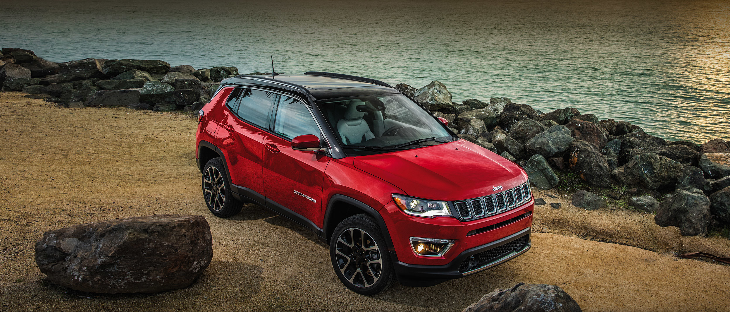 Red 2020 Jeep Compass parked by a river with a city in the background.