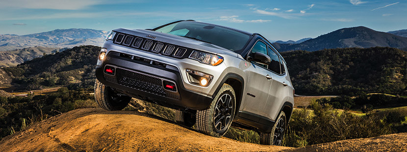 Silver 2020 Jeep Compass driving over hills by the mountains.