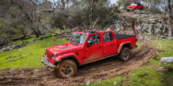 Red 2020 Jeep Gladiator being driven through rocks and mud in the wilderness