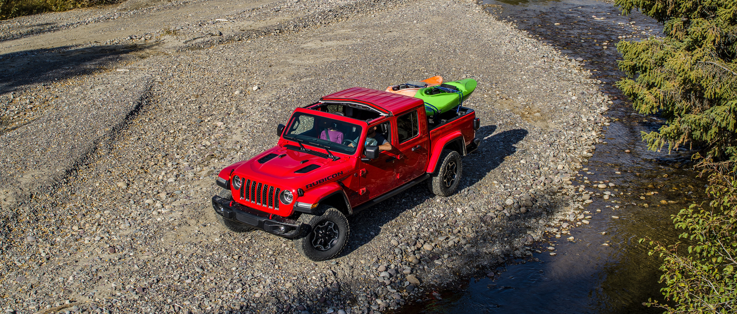 2020 Jeep Gladiator red exterior parked beside a stream
