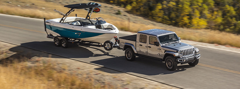 Silver 2020 Jeep Gladiator towing a white-and-blue boat through a plain in the forest, with a lake in the background.