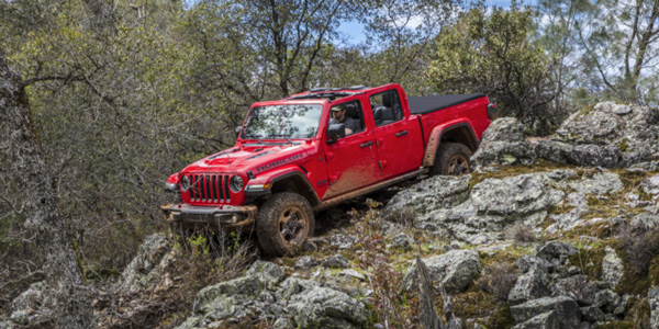 Red 2021 Jeep Gladiator driving through a large rocky hill in the forest