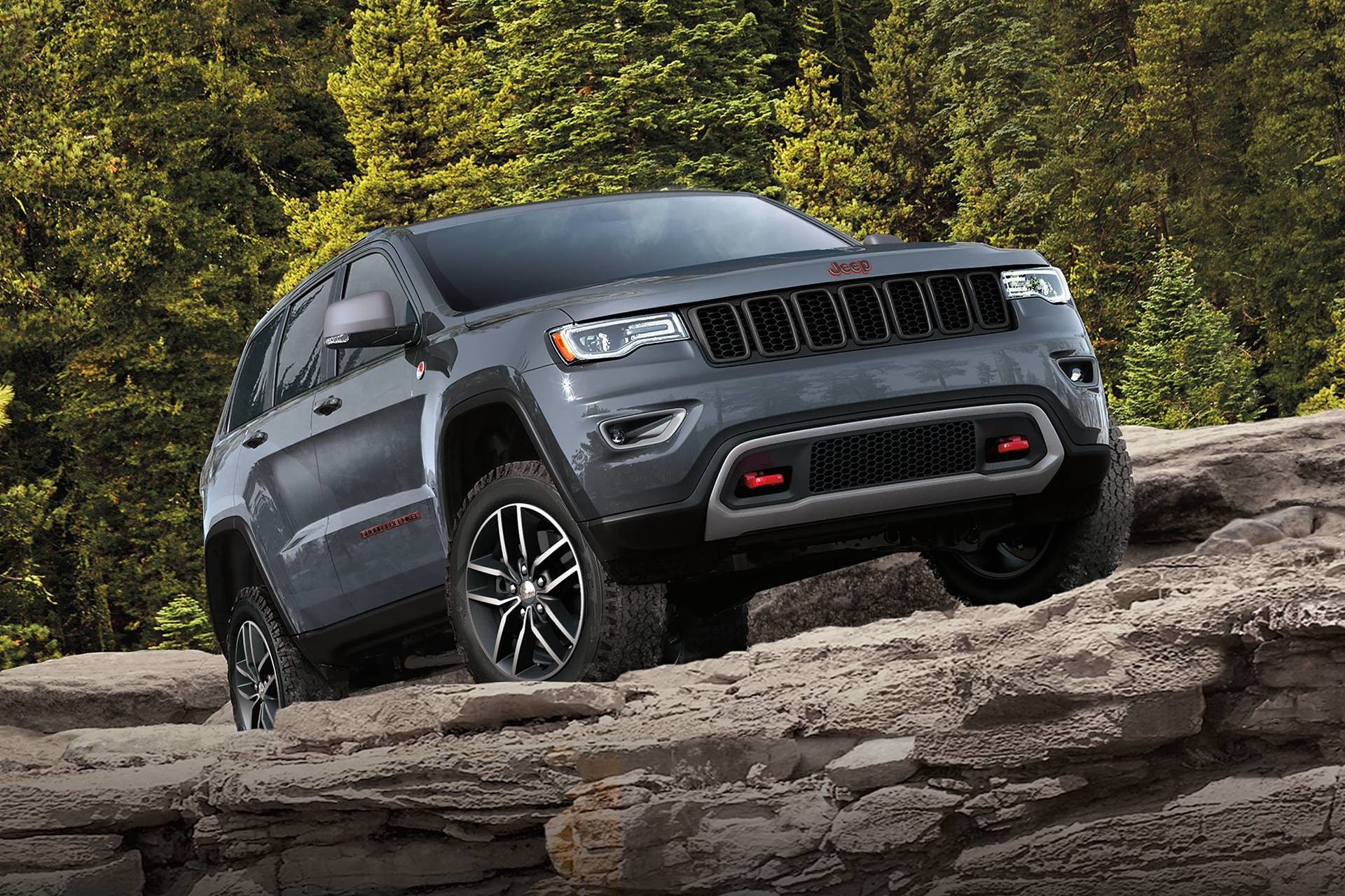 2018 Jeep Grand Cherokee SUV side view, off-road driving on rocks, shown in red