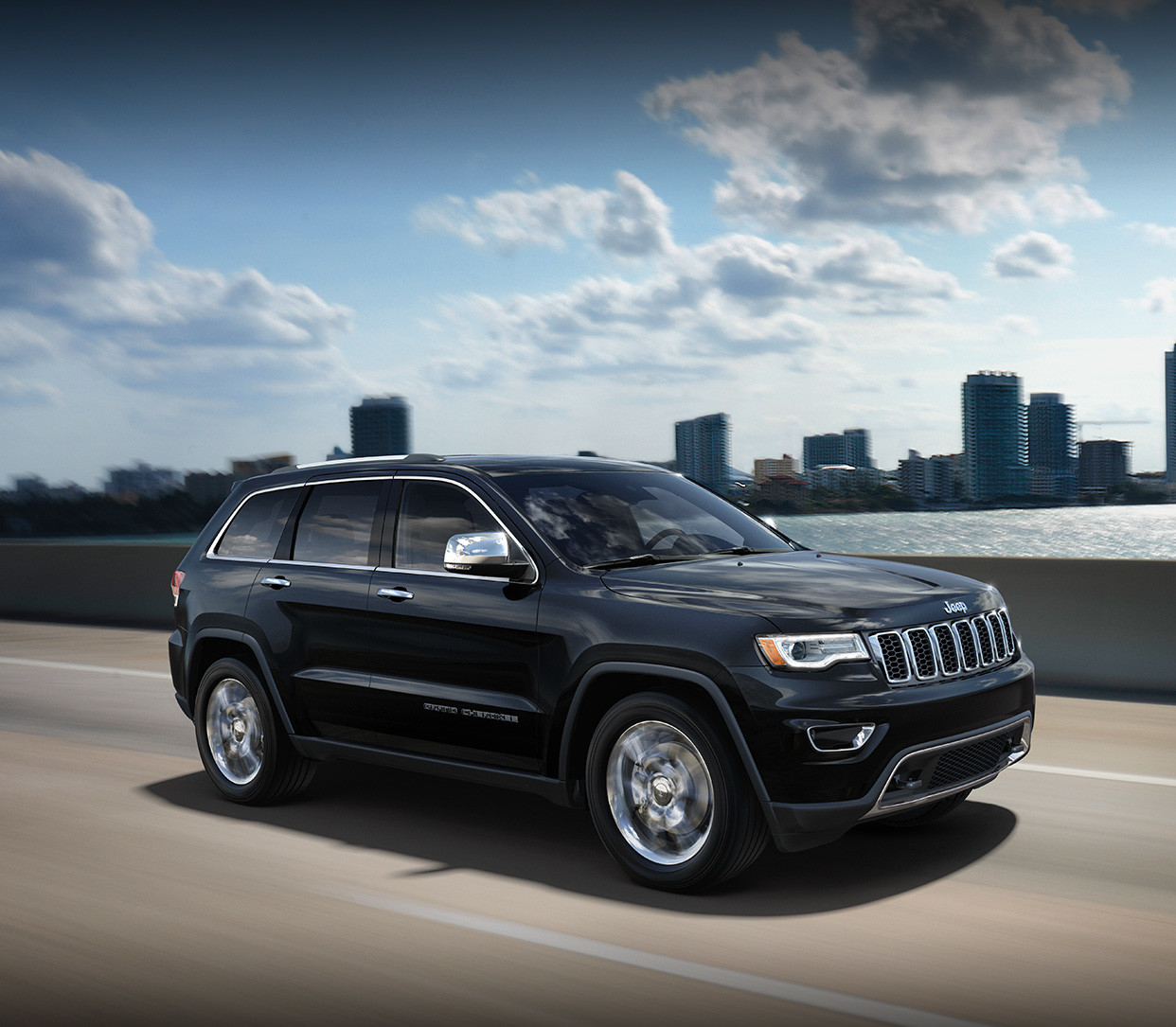 Black 2019 Jeep Grand Cherokee Speeding Through the Roads in Front of a City Skyline