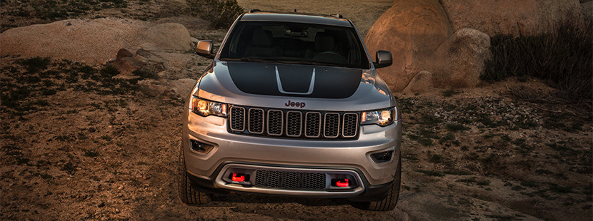 2019 Jeep Grand Cherokee in silver driving over rocks